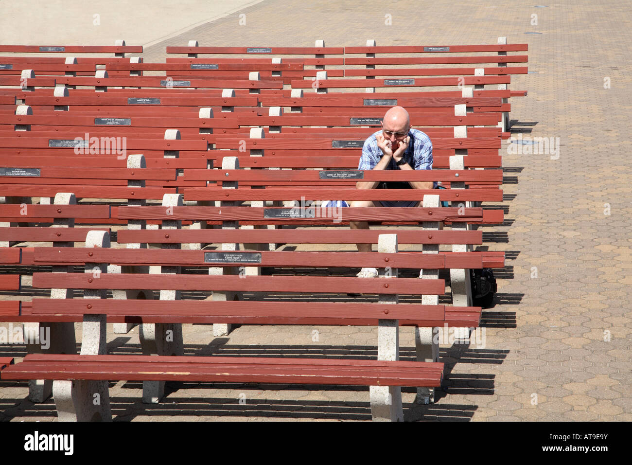 Rows of concrete and wooden seats all empty except one soiltary man sitting on end of row looking very sad and alone. - Stock Image