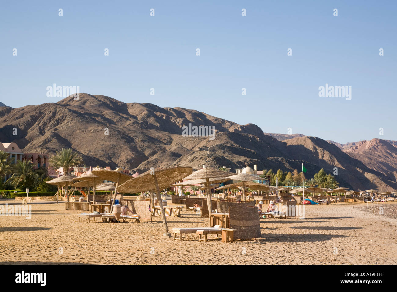 quiet sandy beach with mountain backdrop in taba heights resort on