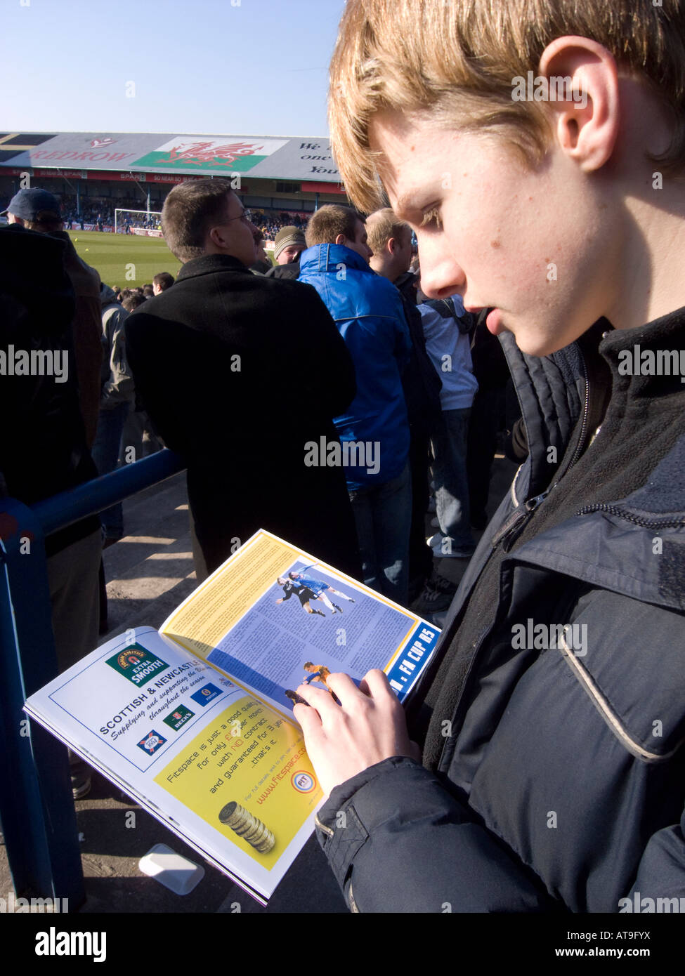 a boy reading a football programme inside Ninian Park Cardiff - Stock Image