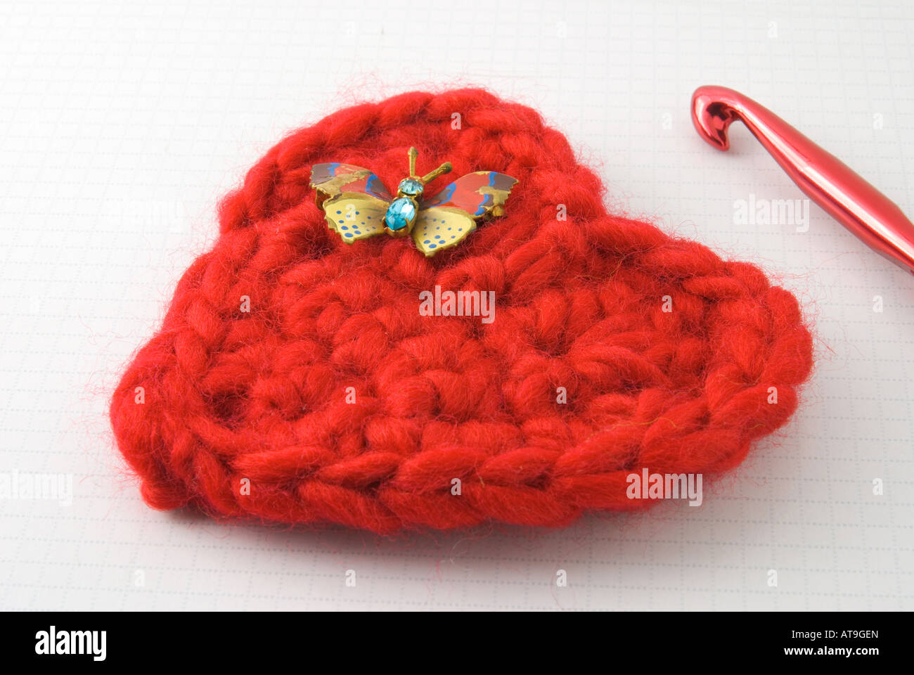 Crocheted red heart with butterfly pin and crochet hook - Stock Image