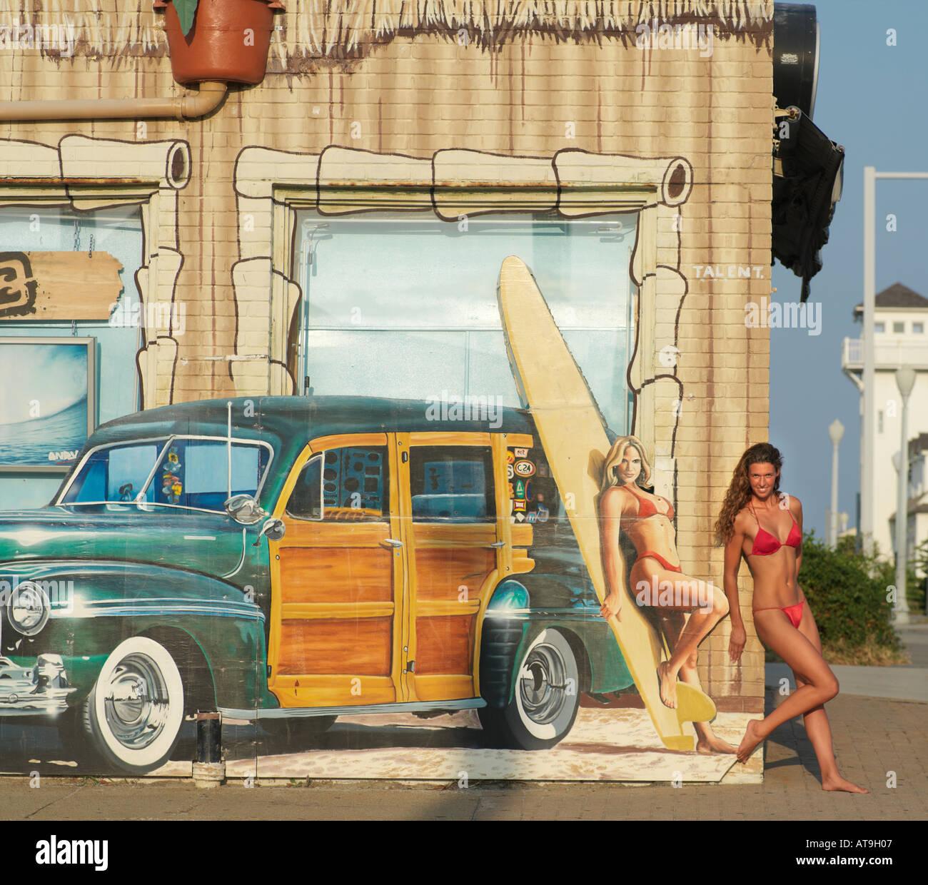 Woman in red bikini mimics woman in wall mural Corner 24 Surf Shop Virginia Beach VA - Stock Image