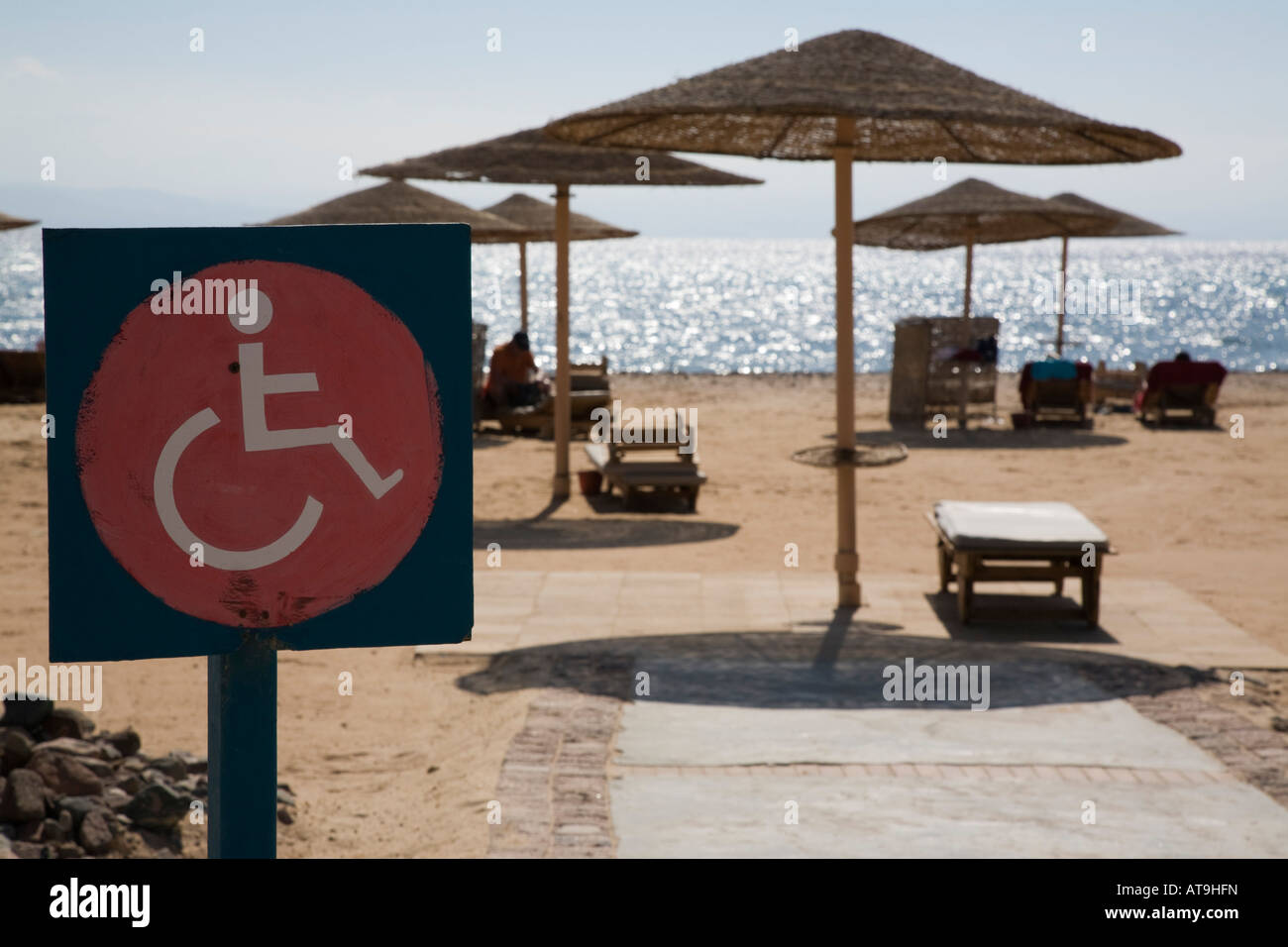 Disability sign by beach sun bed and sunshade with access for disabled wheelchair user on Red Sea Taba Heights Sinai - Stock Image