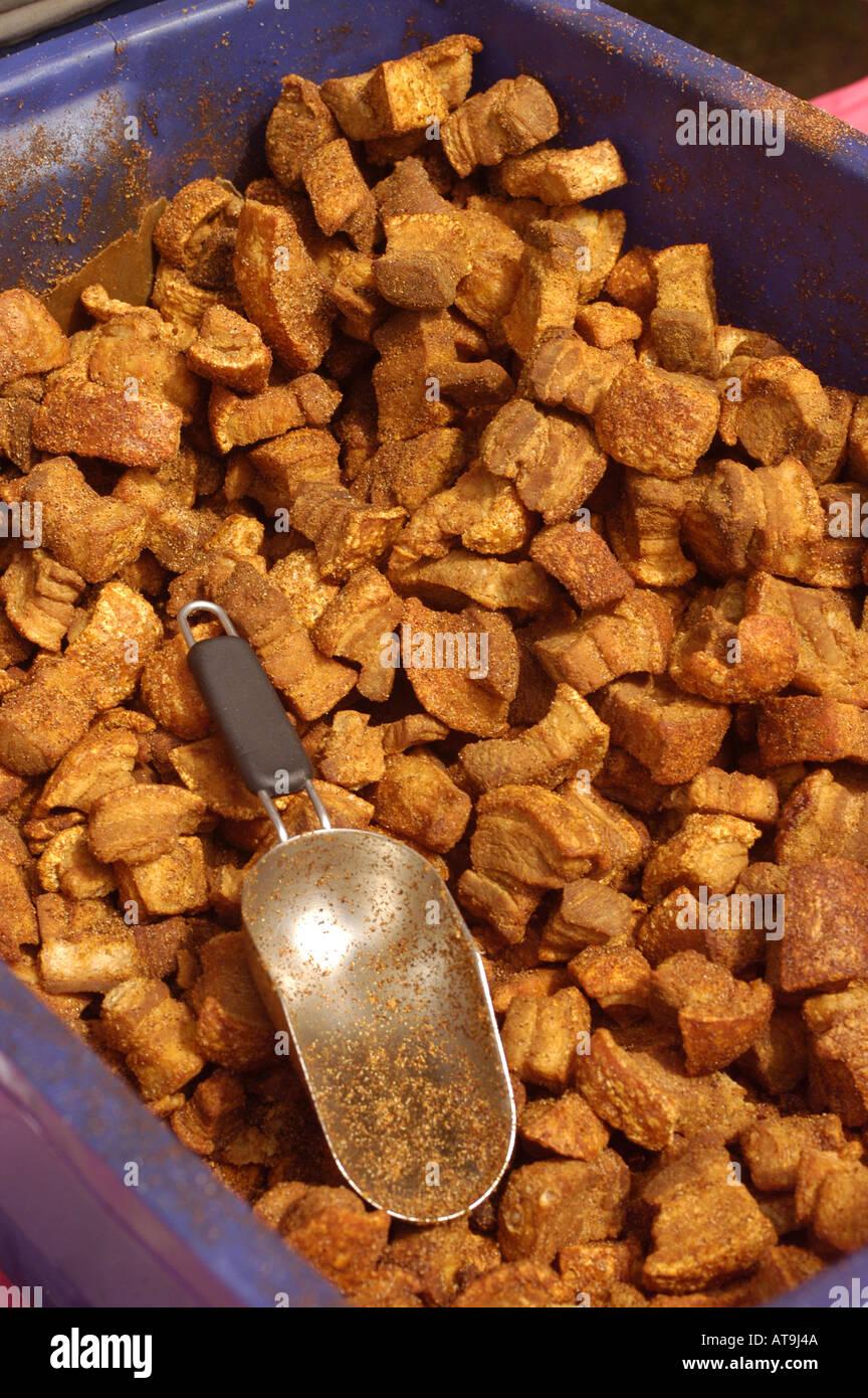 Lafayette Louisiana cajun pork cracklins in plastic purple tub with large scoop - Stock Image