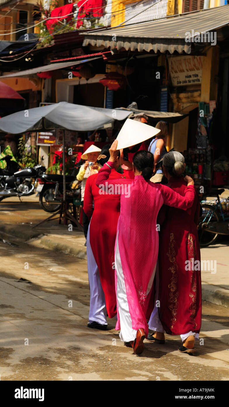 Women going to a Wedding Shelter from the Sun with a Traditional Hat, Hoi An , Vietnam They wear the Traditional - Stock Image