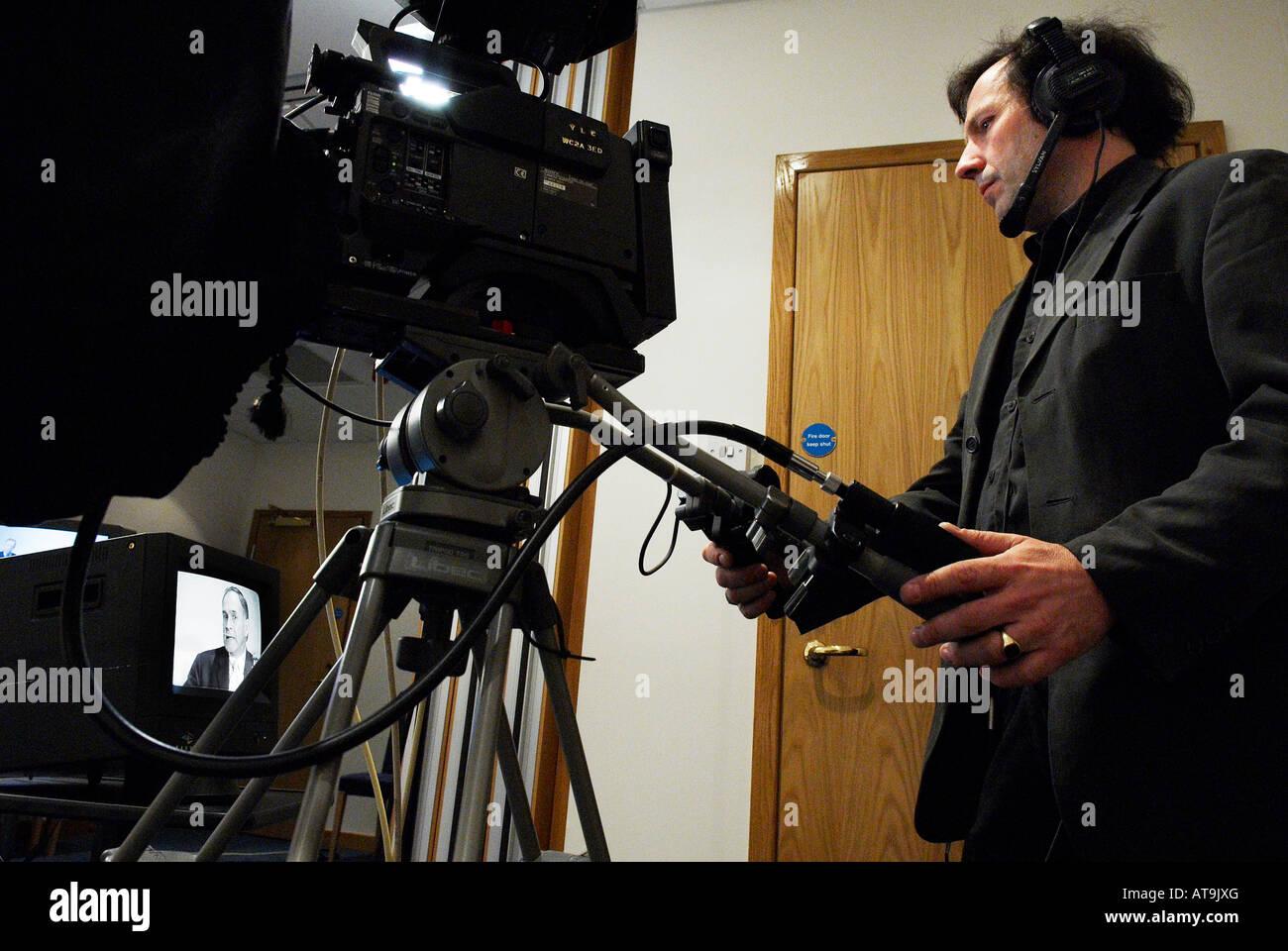 A camera man recording a tv program - Stock Image