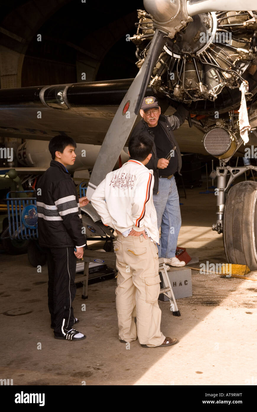 Two Asian Teen Boys Listen to Curator Tell about Plane at Carolinas Aviation Museum in Charlotte NC USA - Stock Image