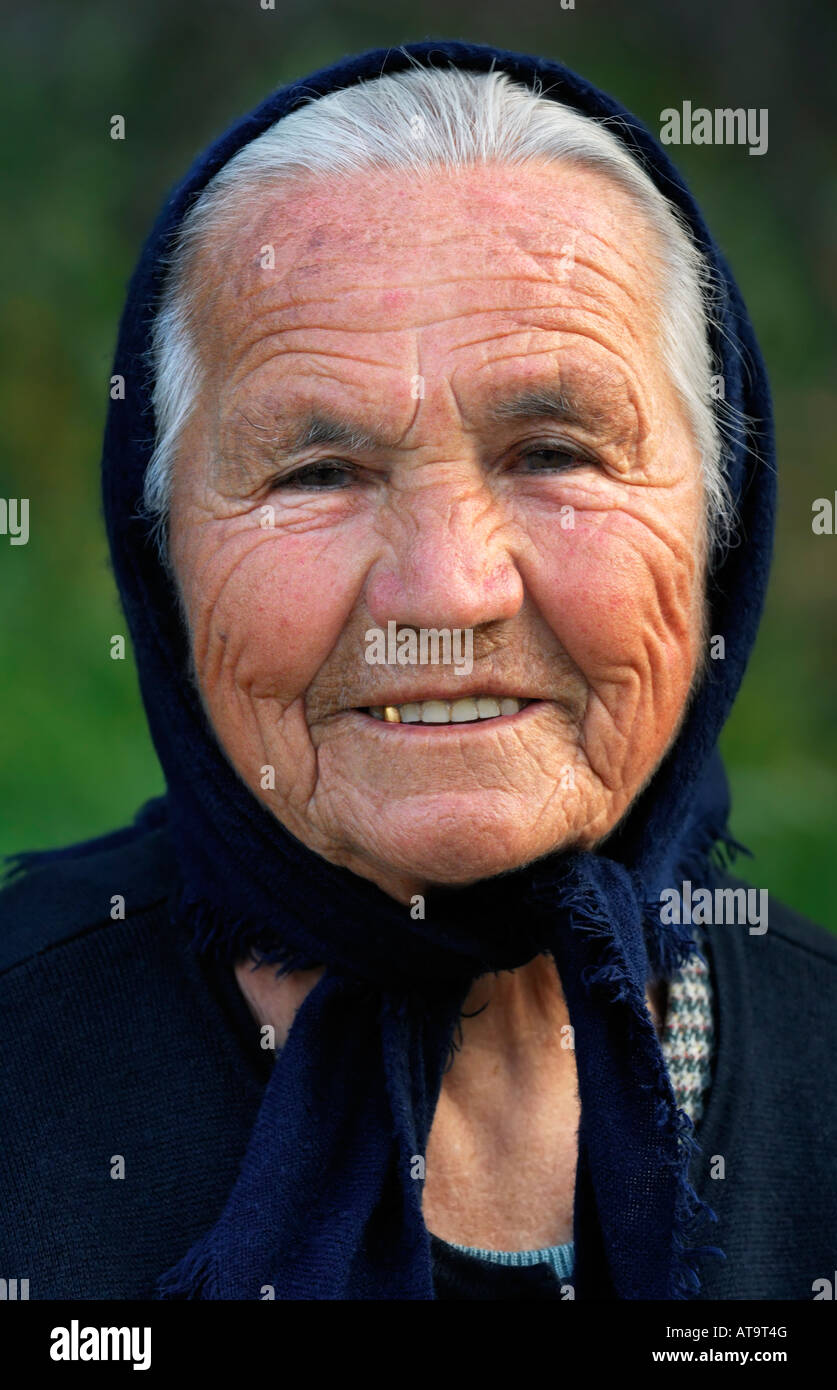 Image shows a portrait of an old smiling Greek lady wearing a scarf - Stock Image