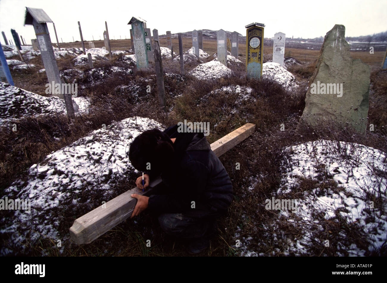 Chechen man marks his friend's grave in a cemetery near Grozny, Chechnya. - Stock Image