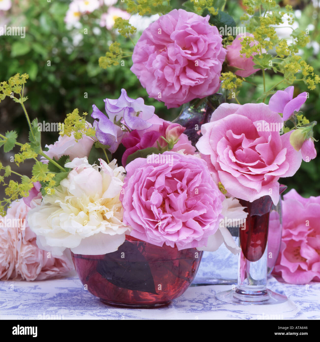 A floral still life with roses paeonies and sweet peas and cranberry glass in an English Garden Stock Photo