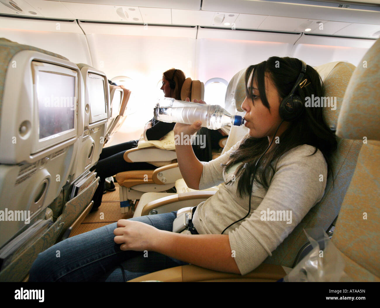 A teenage girl drinks while watching the in-flight entertainment system, Etihad Airways - Stock Image