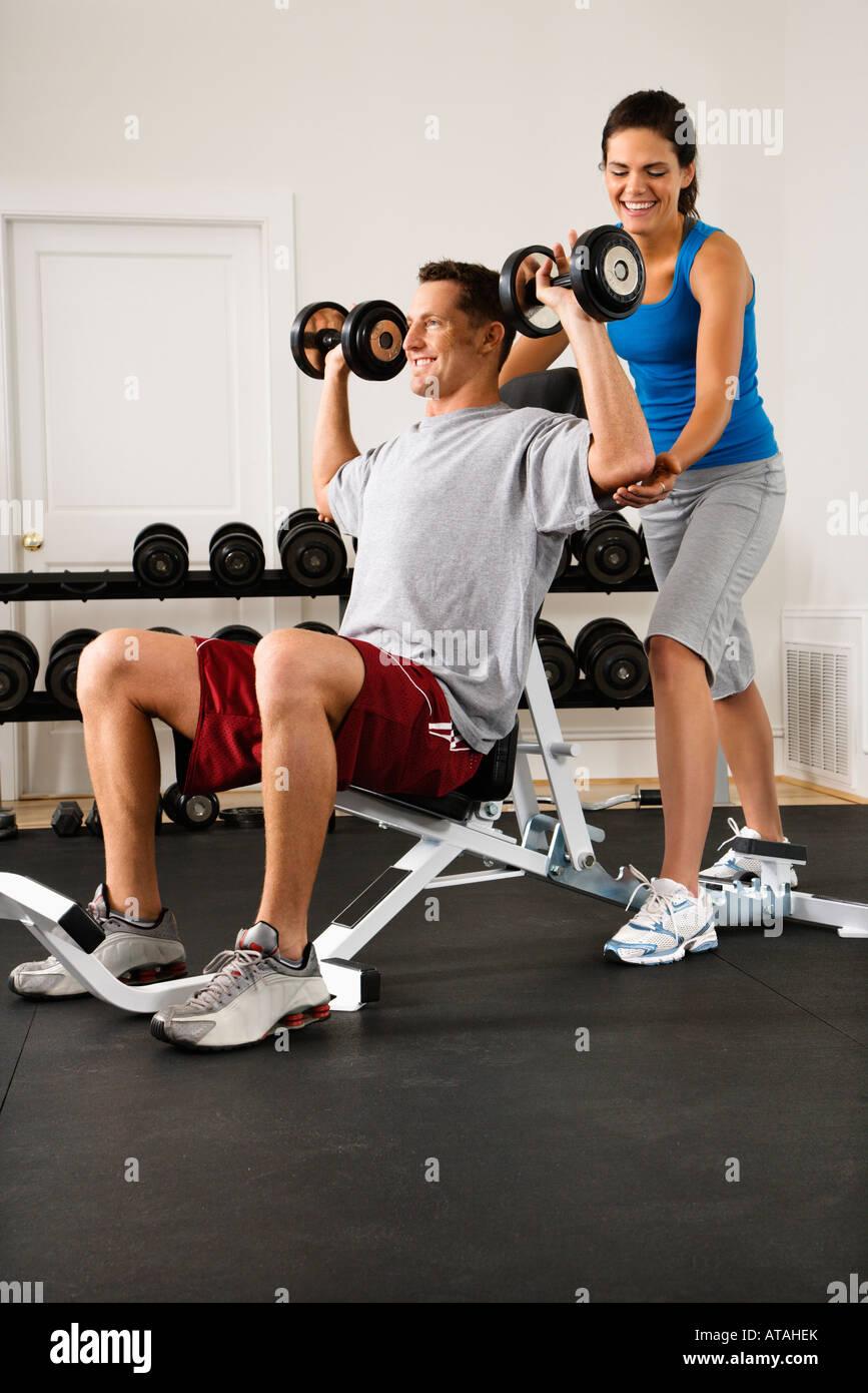 Woman assisting man lifting weights at gym Stock Photo