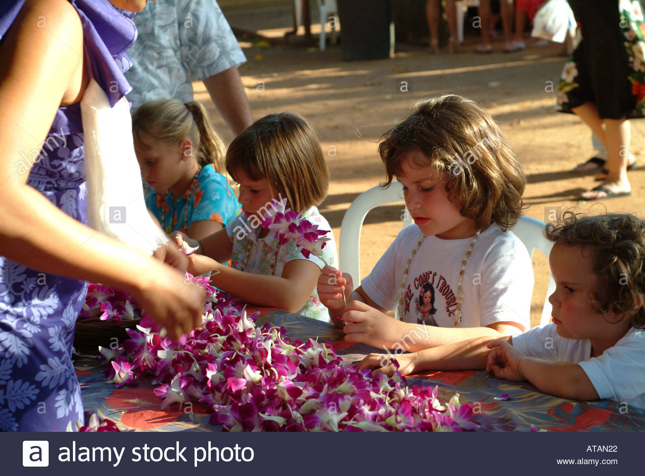 Young vistors learning how to make lei flower necklace stock photo young vistors learning how to make lei flower necklace izmirmasajfo