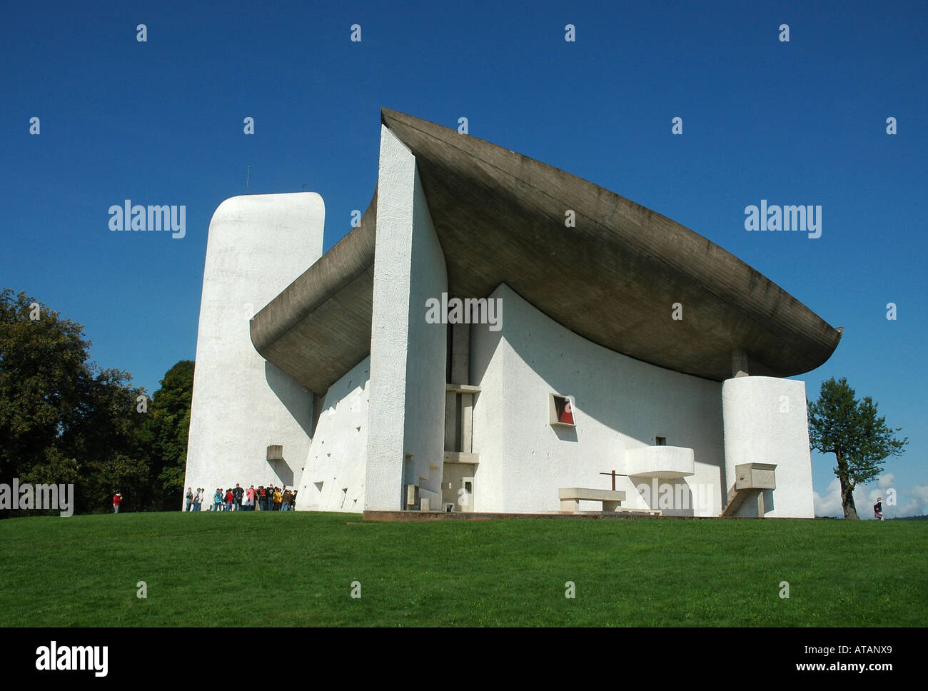 Schoolkids visit the Notre-Dame-du-Haut chapel by architect Le Corbusier on a hillltop above Ronchamp in France's Jura region - Stock Image