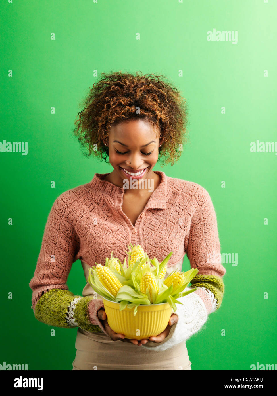 Portrait of pretty young woman standing against green background holding bowl full of ears of corn - Stock Image