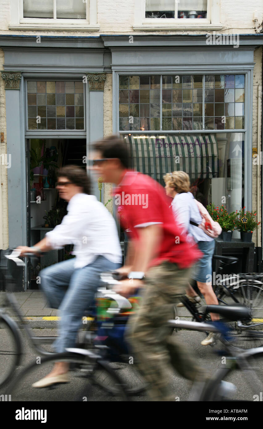 Cyclists go past Blooming art flower shop on the Denneweg in the Hague The Netherlands. Picturesque street with - Stock Image