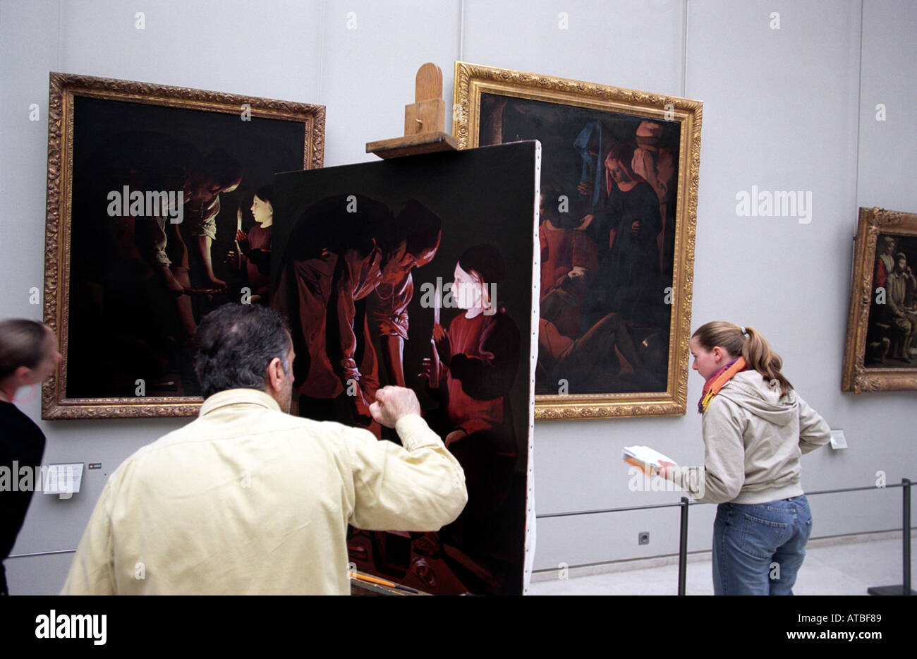 An artist copies a painting in the Louvre museum in Paris France - Stock Image