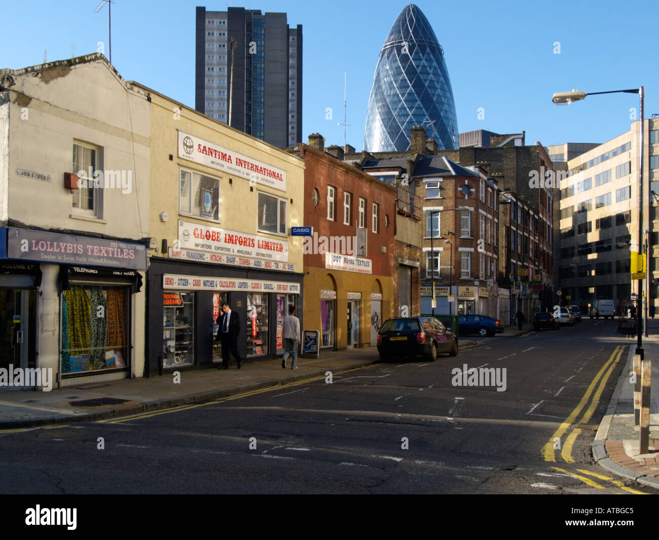 The gherkin Swiss Re building by Sir Norman Foster in the city financial district as seen from a less wealthy area London UK - Stock Image