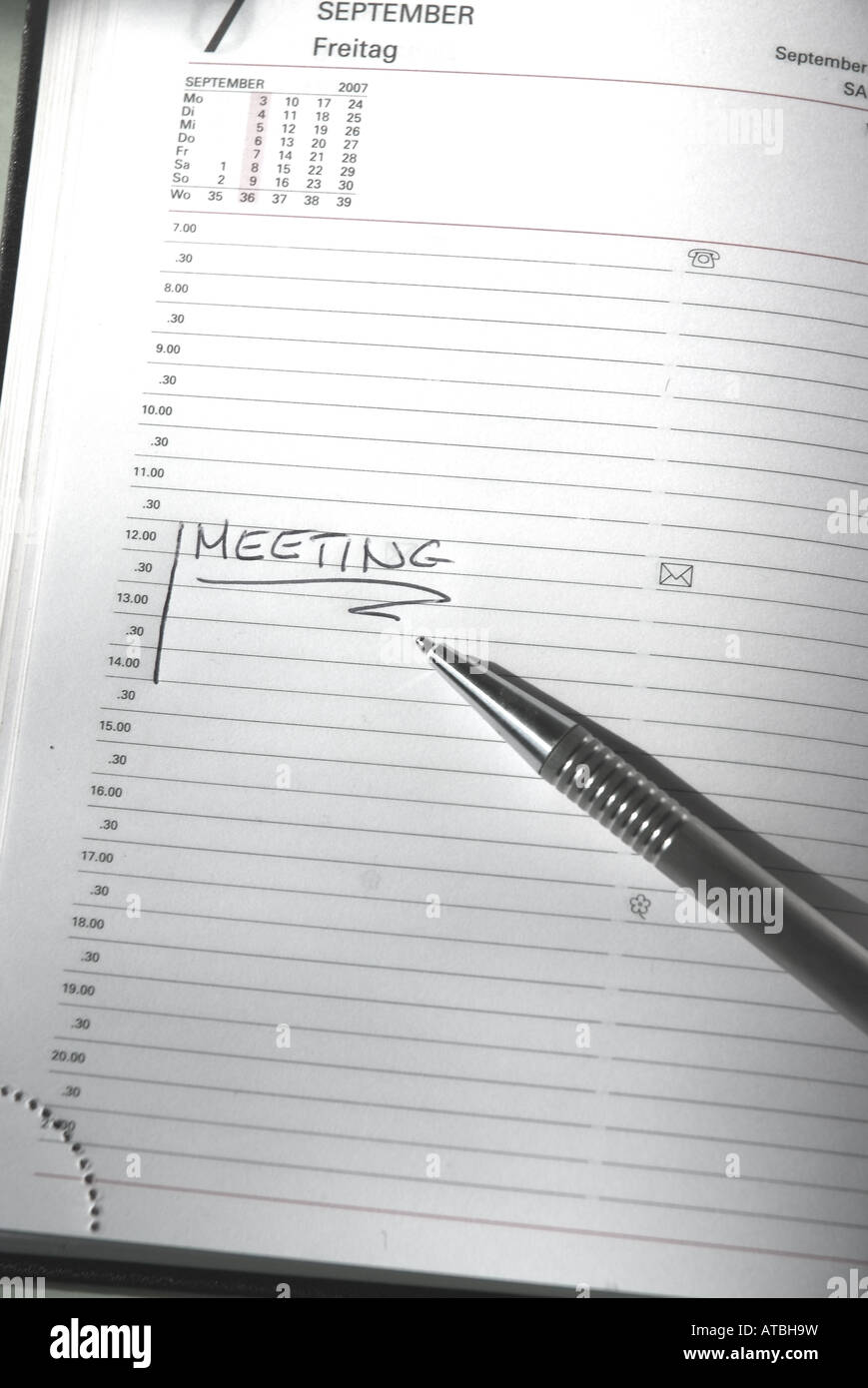 Meeting written on the white paper of a timer with a pen - Stock Image