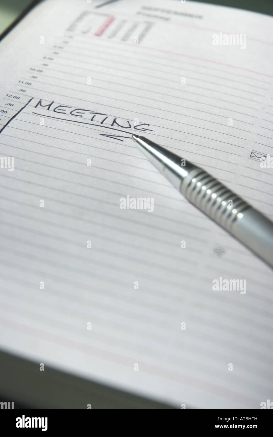 Meeting written in a timer with pencil Close-Up - Stock Image