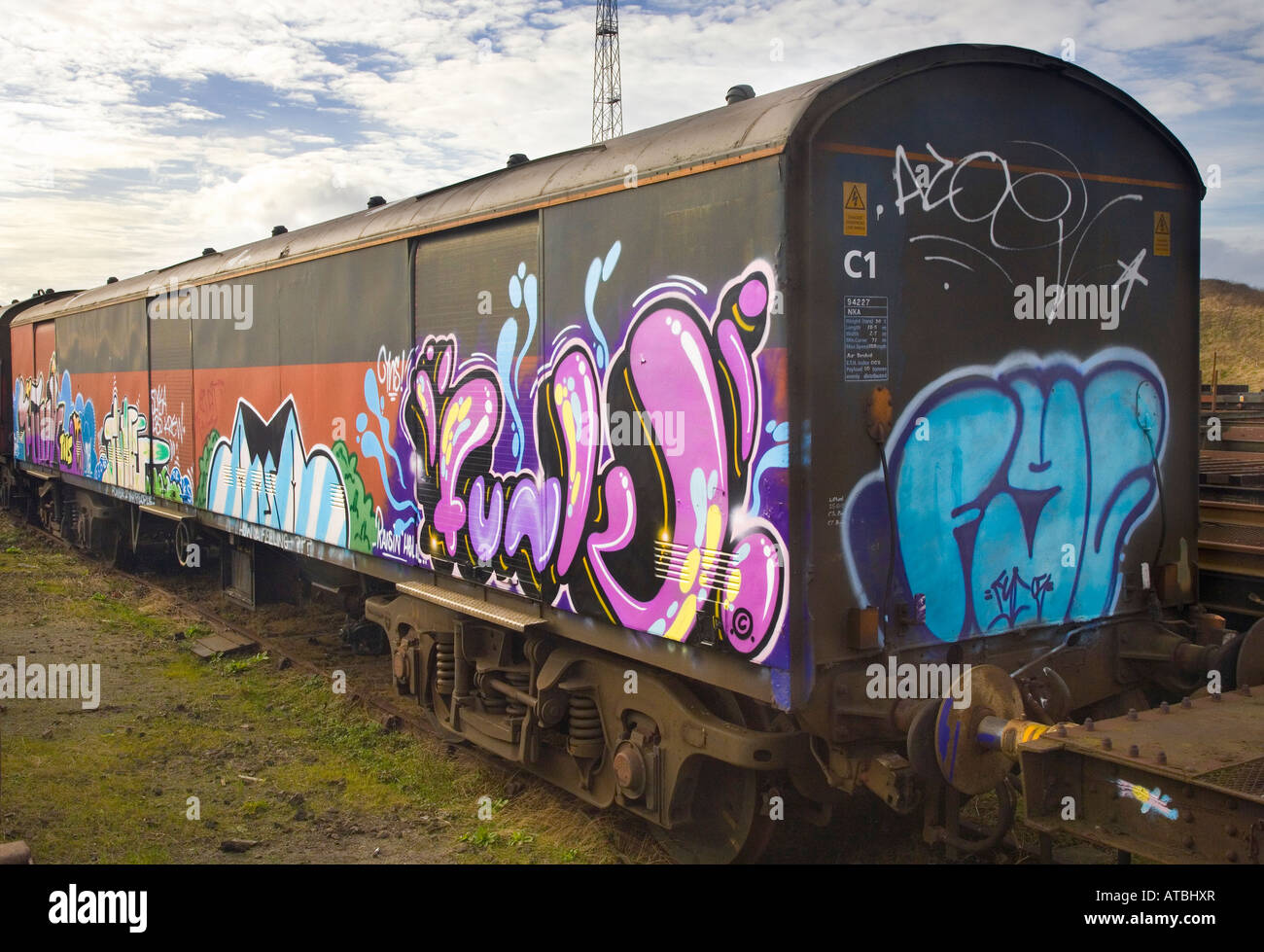 Graffiti subculture painted on trains defaced royal mail railway freight train carriages in siding in