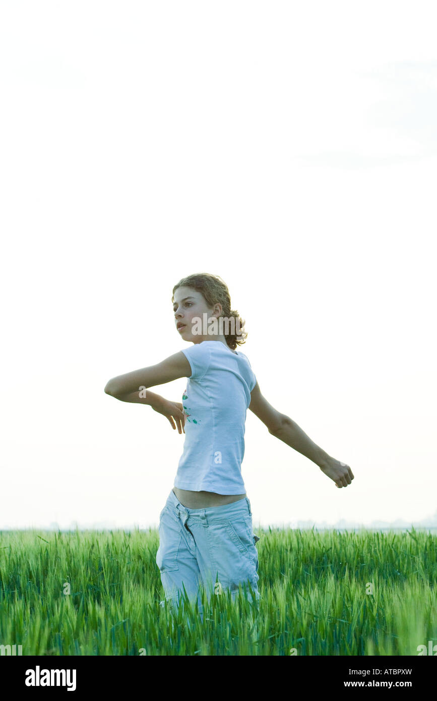 Teenage girl standing in field, doing spinal twist - Stock Image