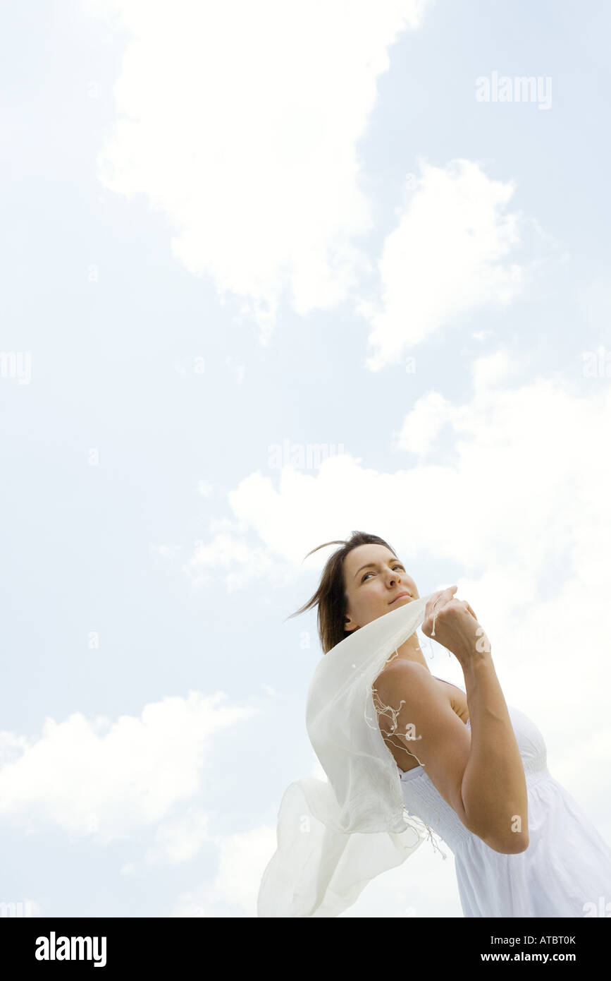 Woman holding up shawl outdoors, tousled by wind, low angle view - Stock Image