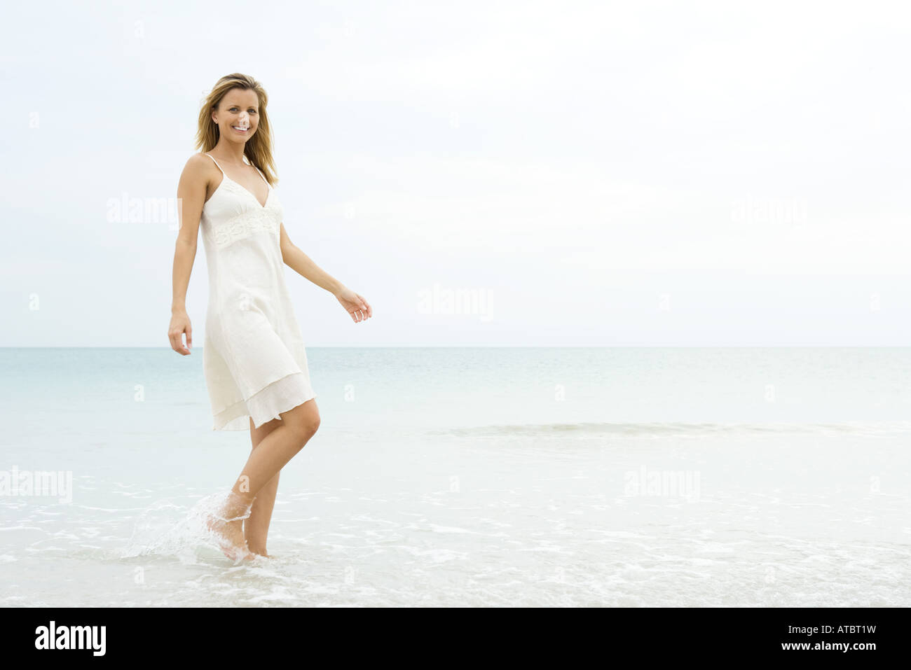 Young woman in sundress walking in shallow water, smiling at camera - Stock Image