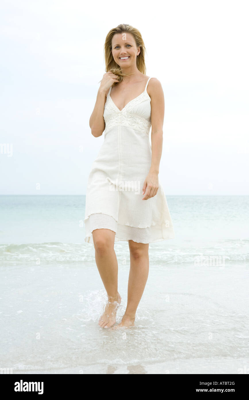 Woman in sundress walking in surf, hand in hair, smiling at camera - Stock Image