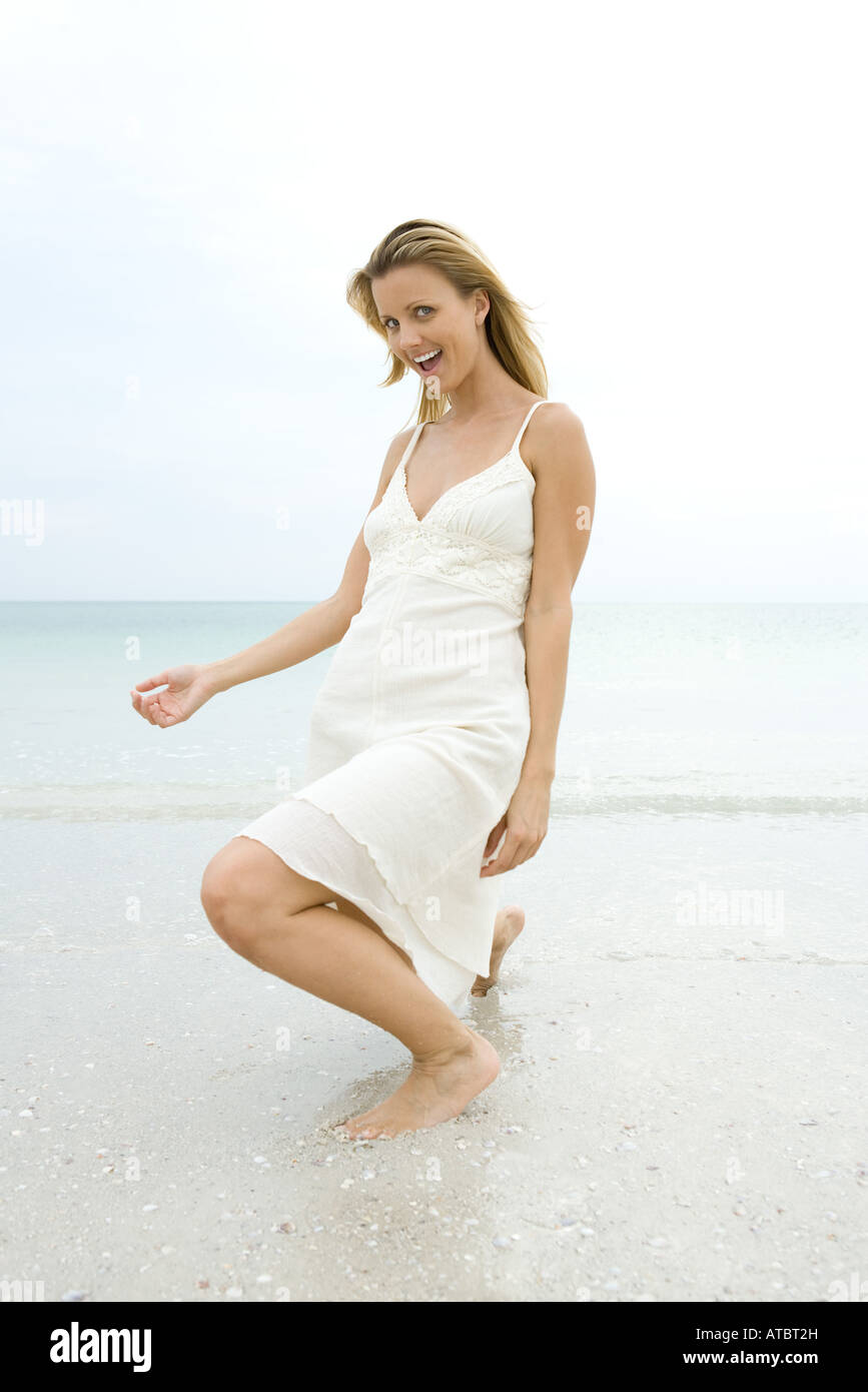 Young woman in sundress crouching in surf, making face at camera - Stock Image