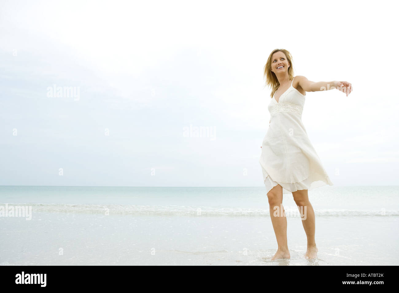 Young woman in sundress walking in surf, arms out, looking away - Stock Image