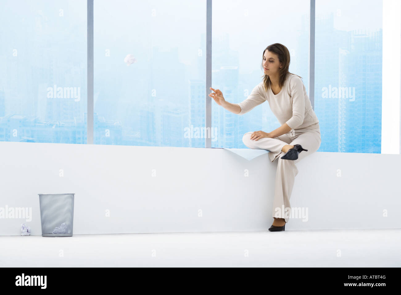 Woman throwing paper ball toward trash can - Stock Image