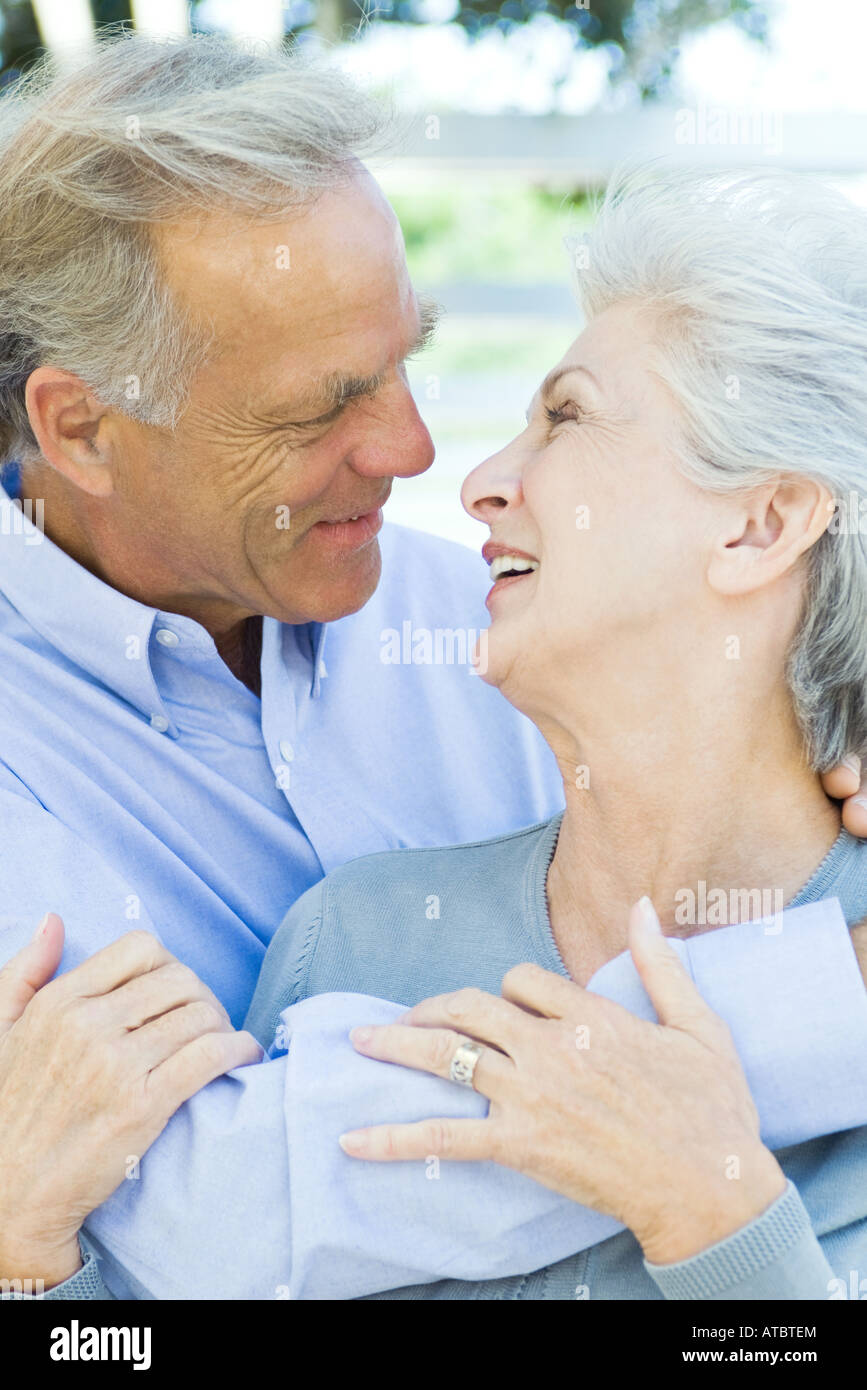 Mature couple embracing, smiling at each other, close-up - Stock Image