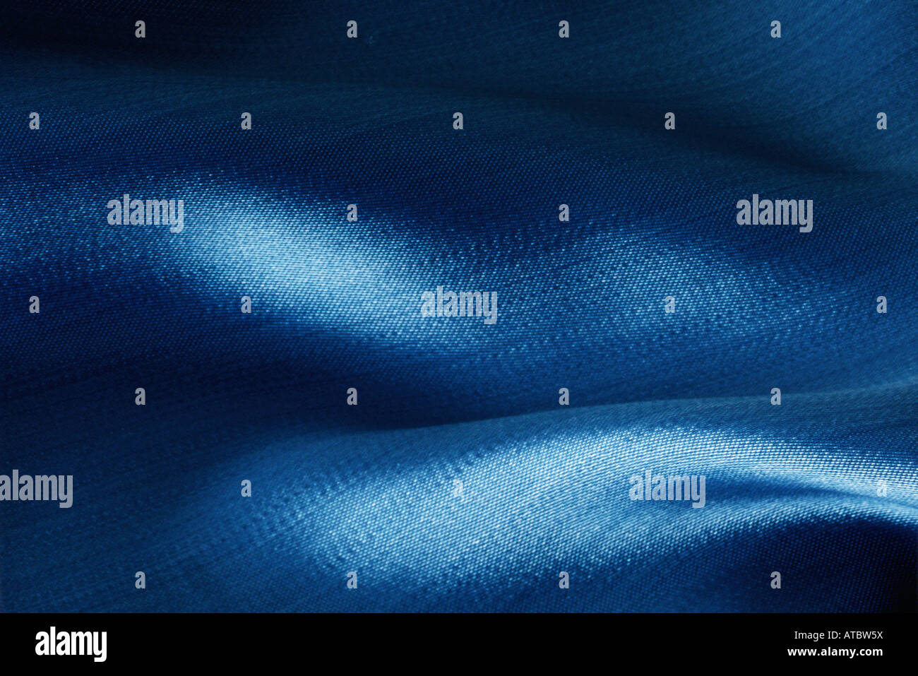 Folds in blue fabric, close-up - Stock Image