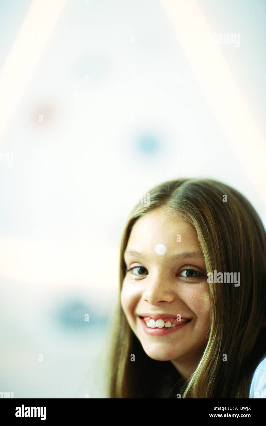 Little girl with white dot on her forehead, smiling at camera, portrait - Stock Image
