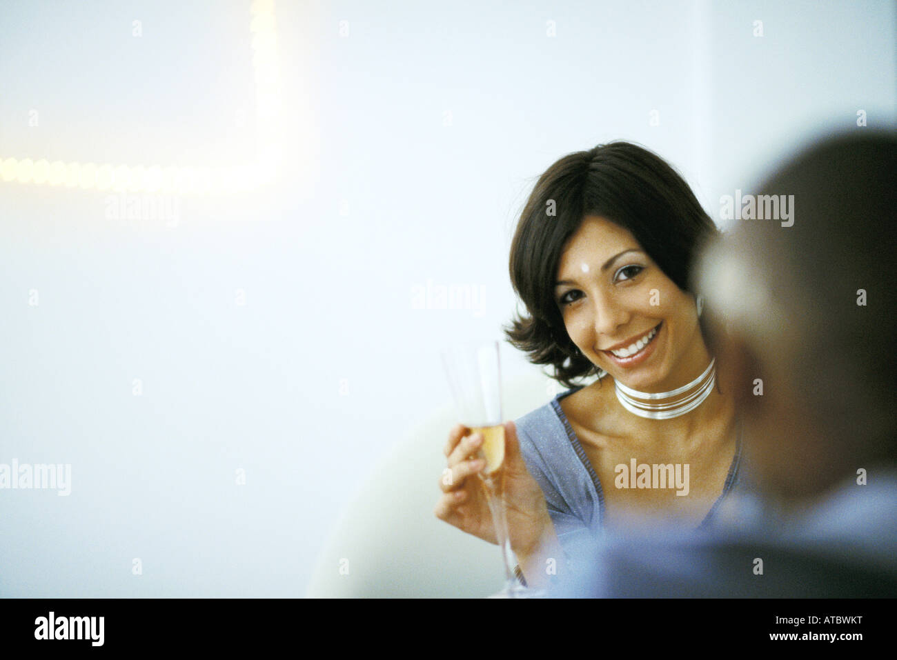 Woman holding champagne glass, smiling at camera, man in foreground - Stock Image