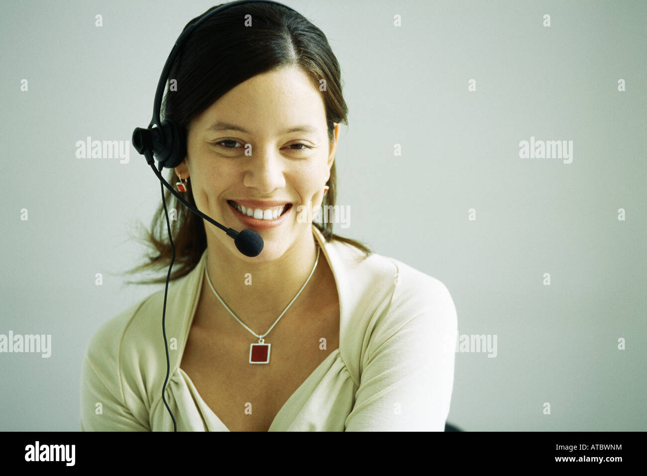 Woman wearing headset, smiling at camera, portrait - Stock Image