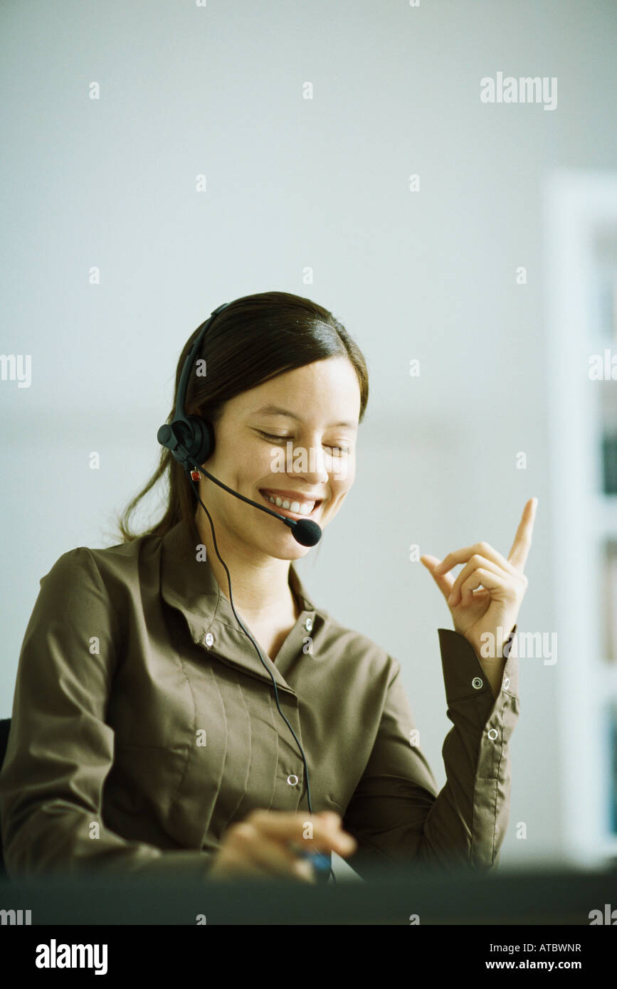 Woman wearing headset, index finger raised, smiling, looking down - Stock Image