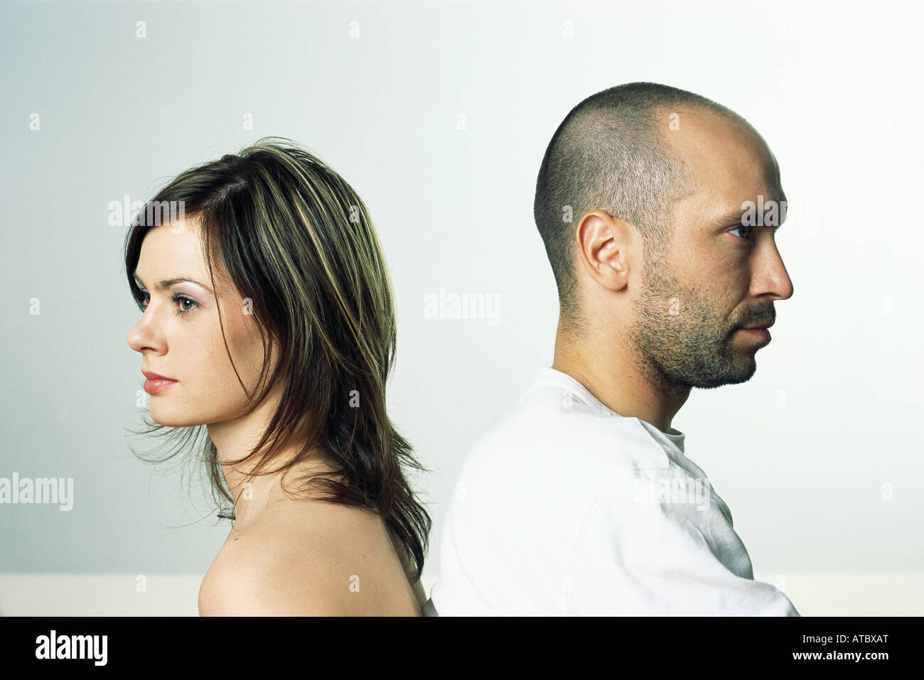 Couple back to back, both looking away, side view - Stock Image