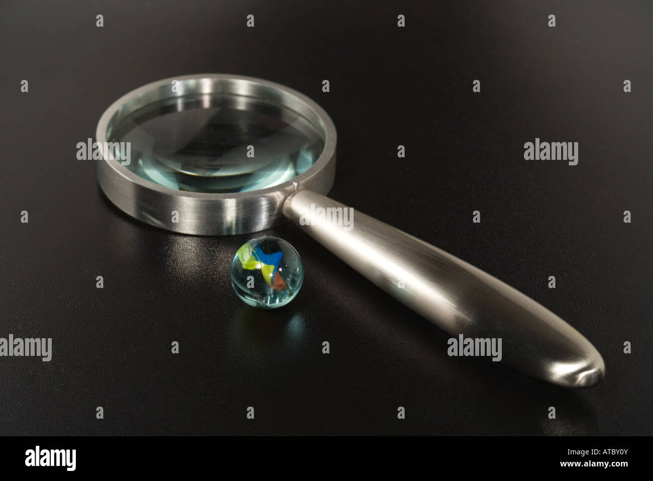 Glass marble and magnifying glass, close-up - Stock Image