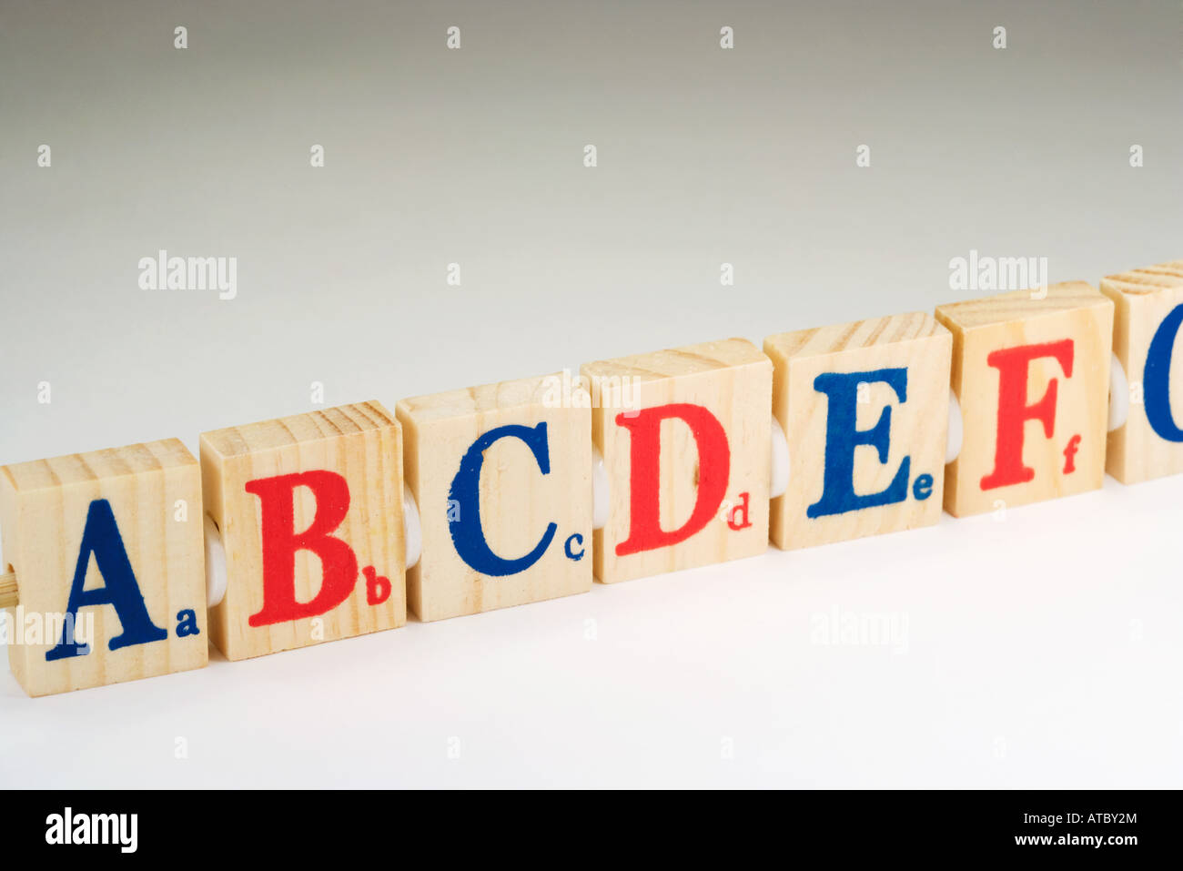 Wooden alphabet blocks in a row, close-up - Stock Image