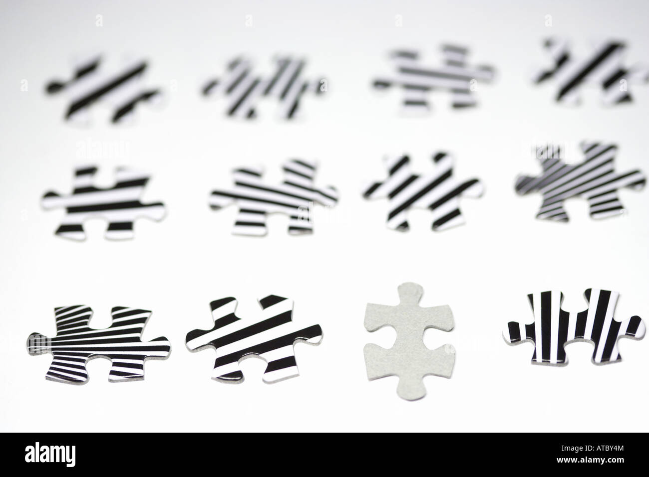 Puzzle pieces lined up, one blank, the others striped, close-up - Stock Image
