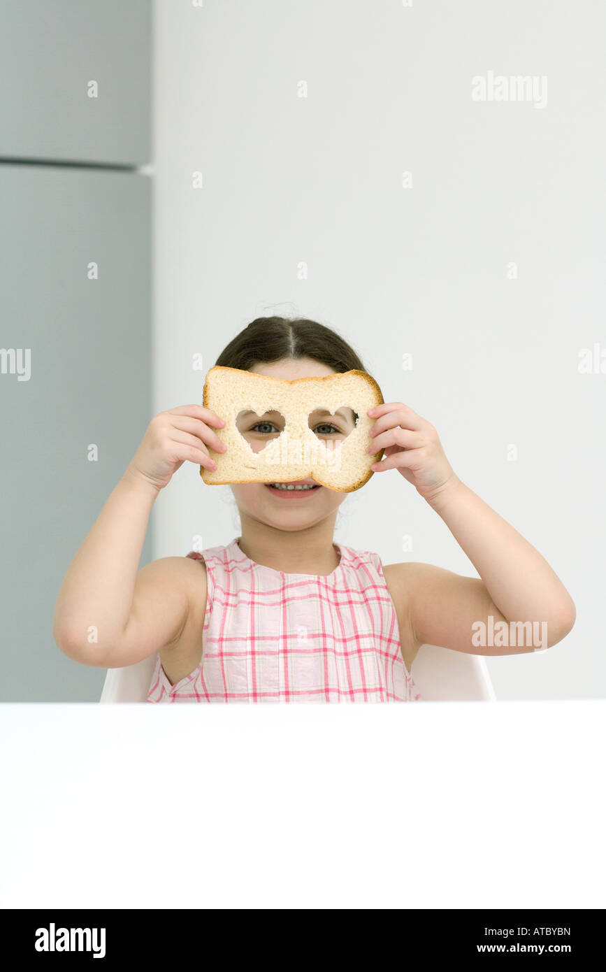 Little girl holding up bread with heart shaped cut outs, looking through holes at camera - Stock Image