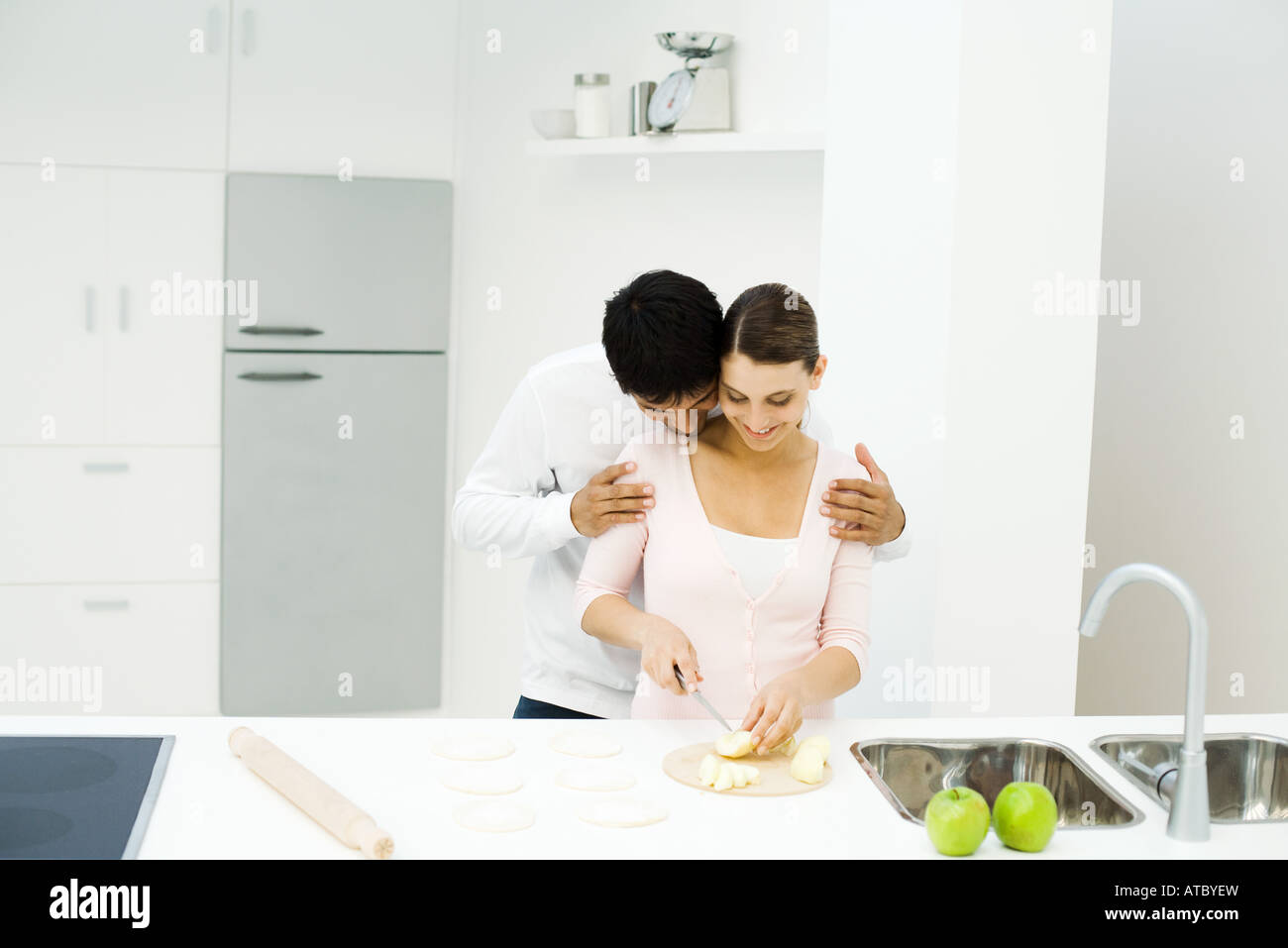 Couple standing together in kitchen, woman cutting apples, man leaning head on her shoulder - Stock Image