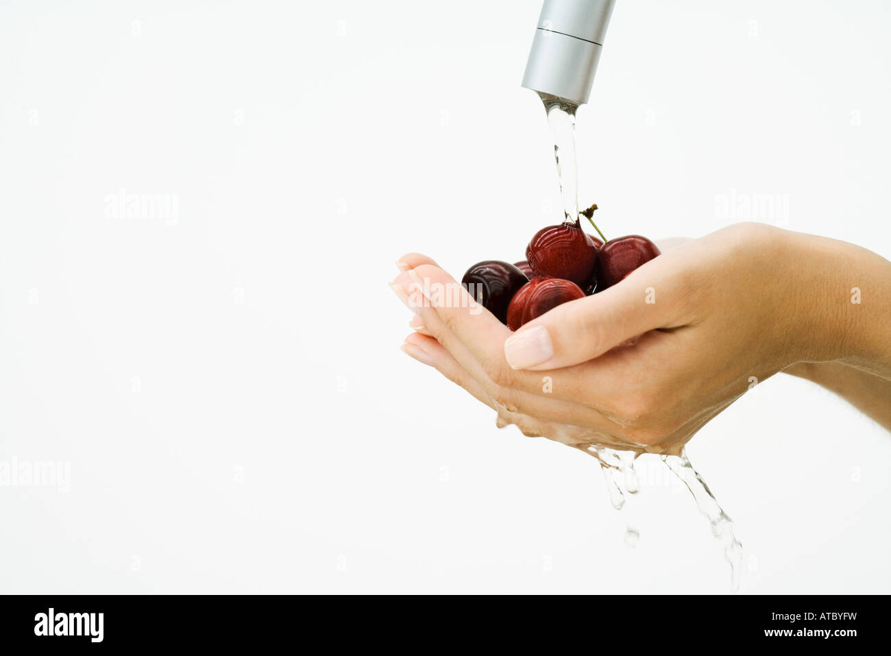 Woman washing handful of tomatoes under faucet, cropped view of hands, close-up - Stock Image