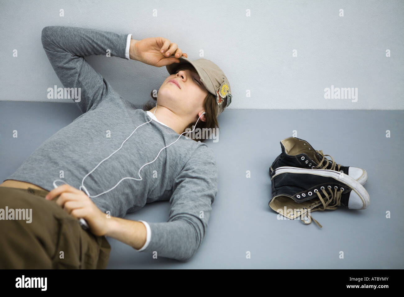 Young man lying on the ground with eyes closed, listening to earphones - Stock Image