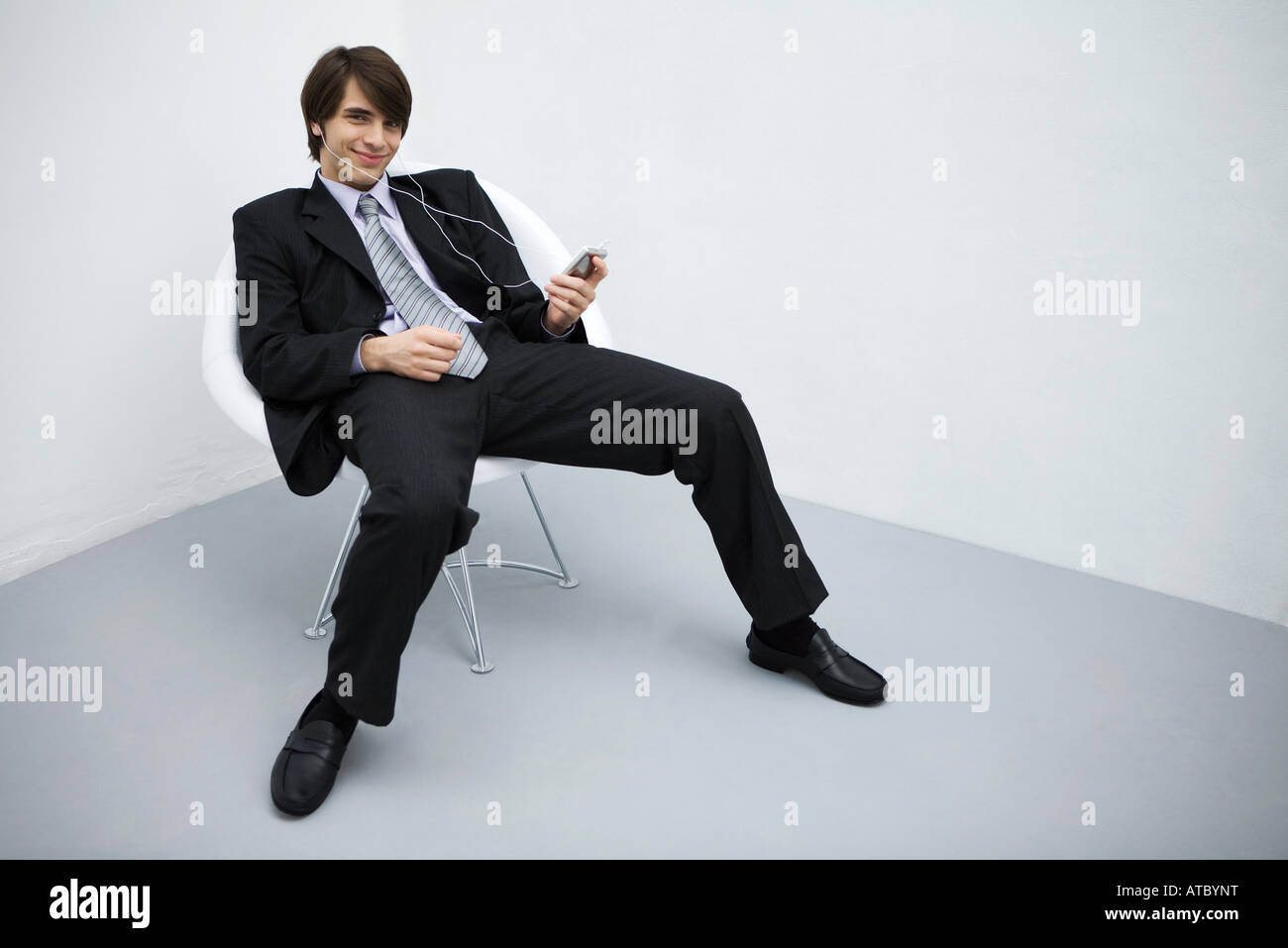 Young man in suit leaning back in chair, listening to mp3 player, smiling at camera, full length Stock Photo