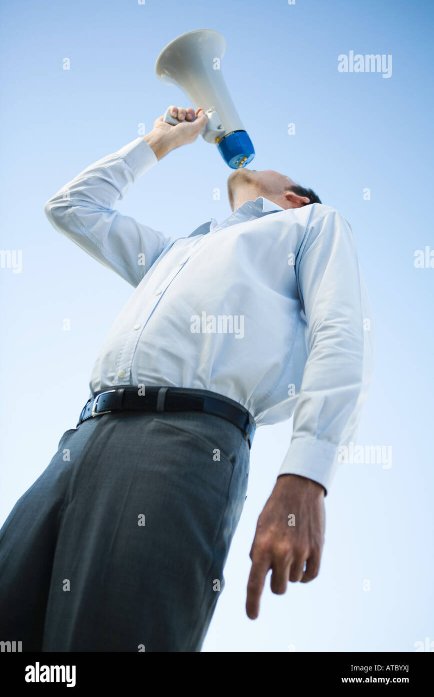 Businessman shouting into megaphone, low angle view - Stock Image