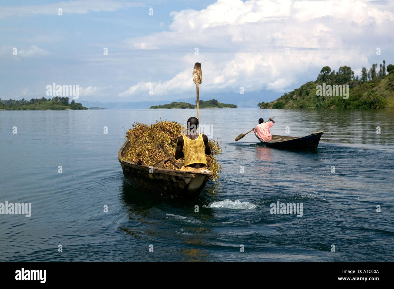 Traditional boatmen carrying soya and other crops in their wooden boats on Lake Kivu in Rwanda Central Africa - Stock Image