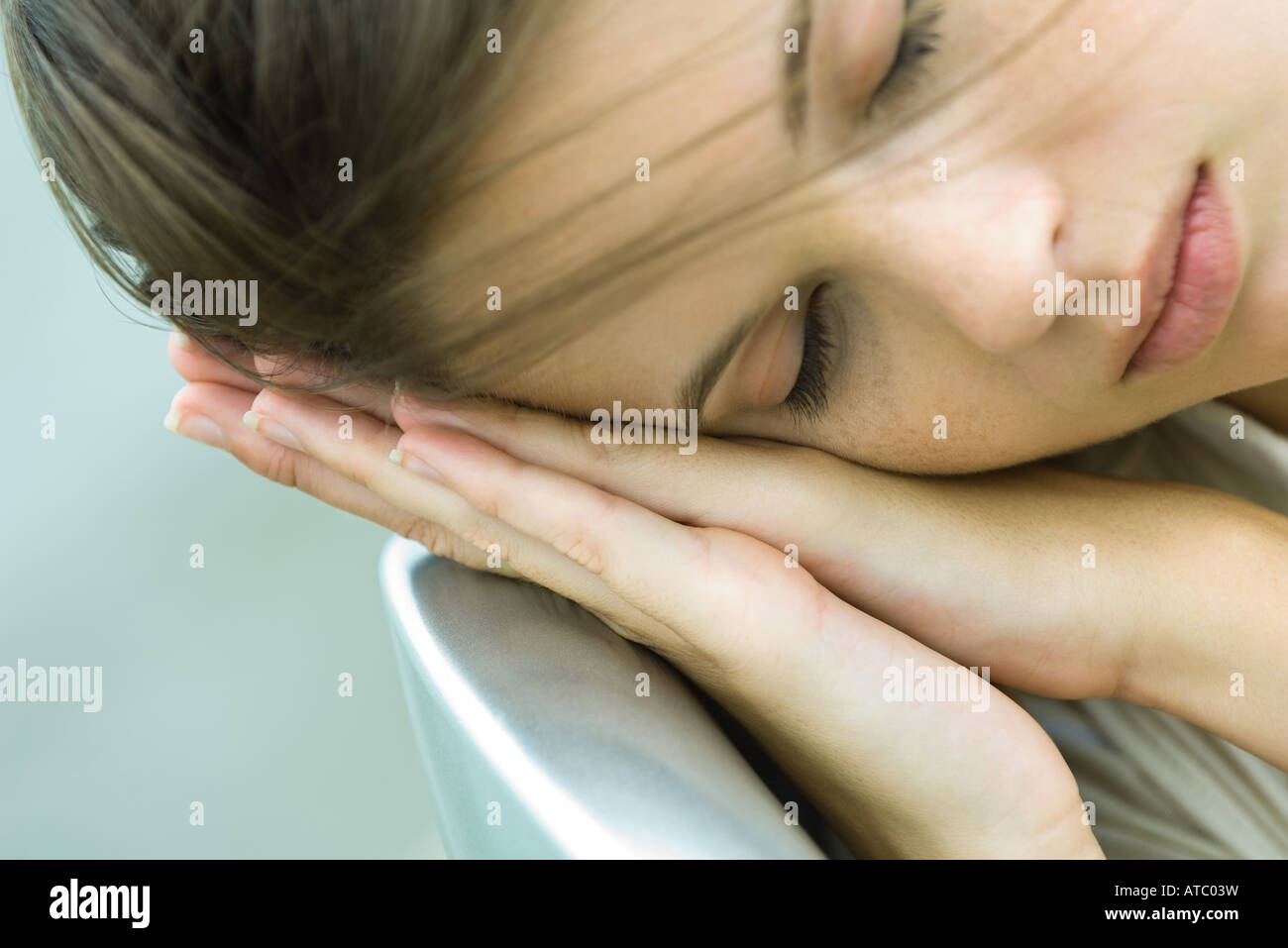 Teenage girl resting head on clasped hands, eyes closed, close-up - Stock Image