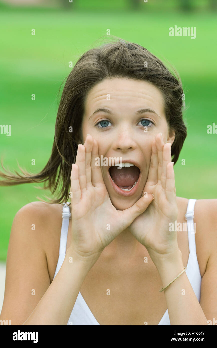Teenage girl shouting, hands raised to mouth, looking at camera - Stock Image